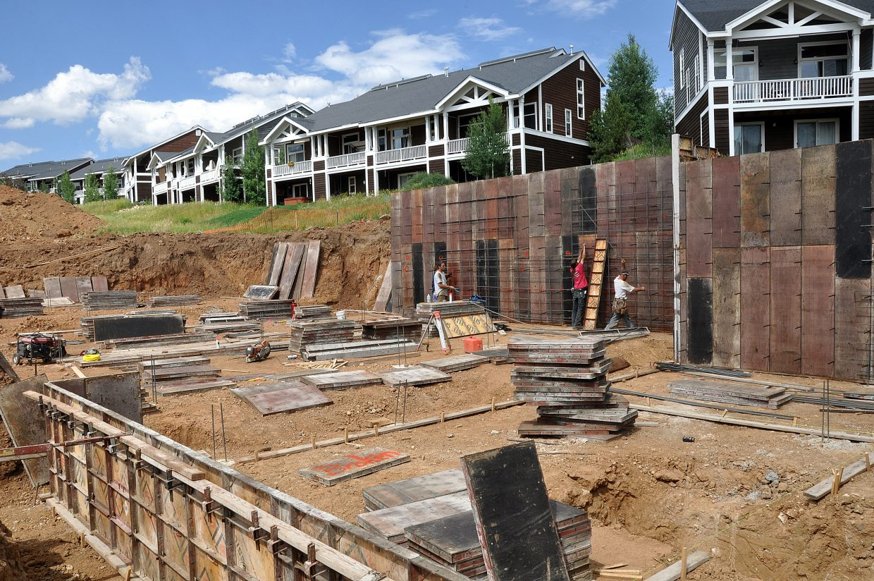 Carpenters work on the foundation of the Emerald Heights townhomes on Monday. The housing project is likely to become one of the first that will not have to abide by the seven-year-old community housing rules that have been criticized by developers and city council members.