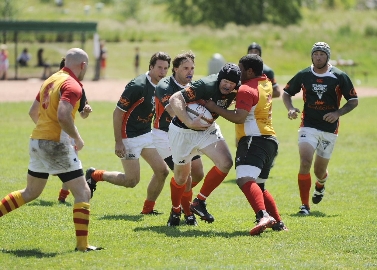 Steamboat Springs rugby player Jay Lawton tries to tackle his way down the field during Saturday's 2011 Cow Pie Classic Rugby Tournament.