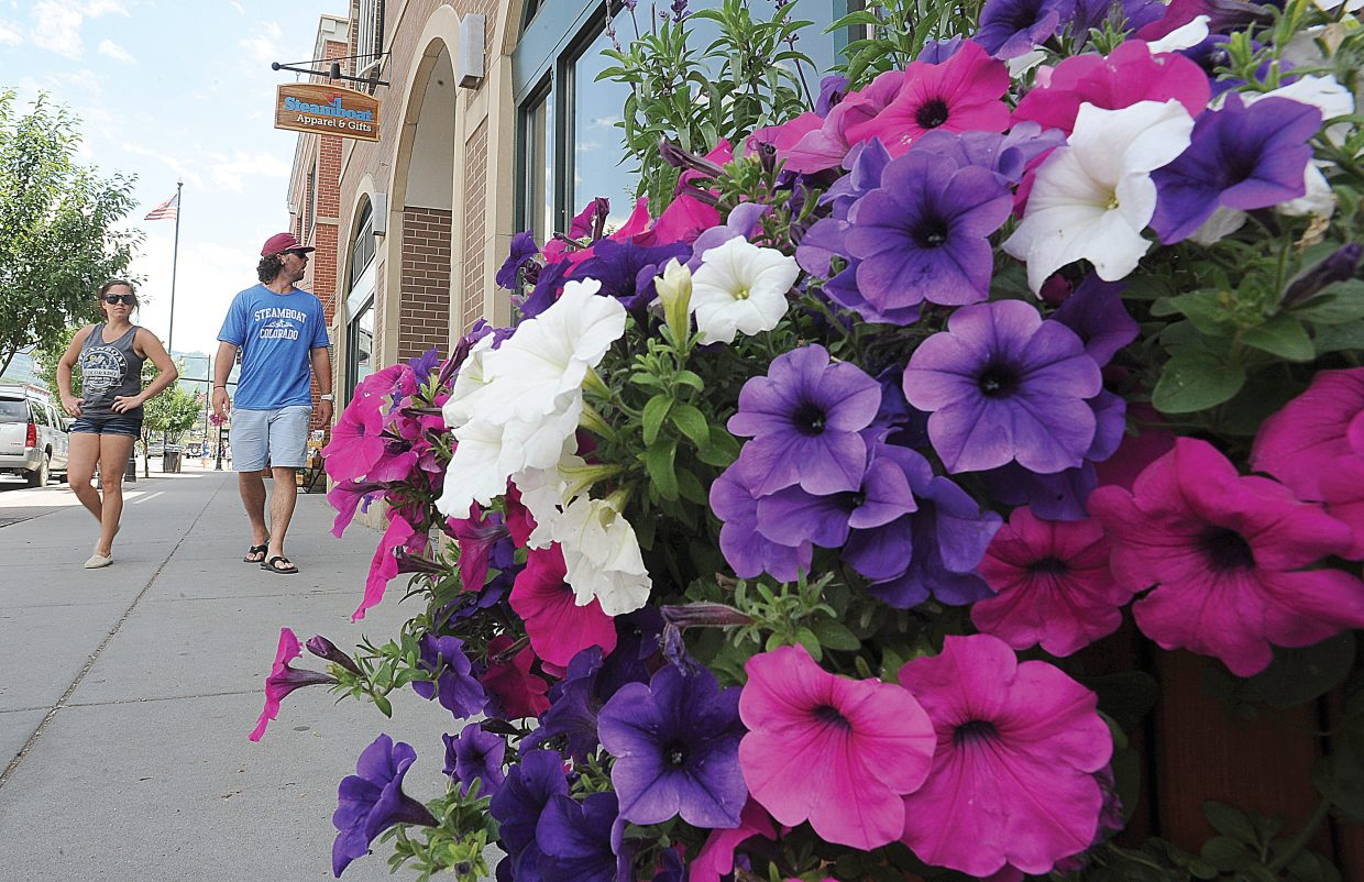 Seattle residents Andrew Braunz and Miranda Rosebrook walk past stores on Lincoln Avenue on Tuesday afternoon. Recent brainstorming sessions on downtown have focused on improving aesthetics.