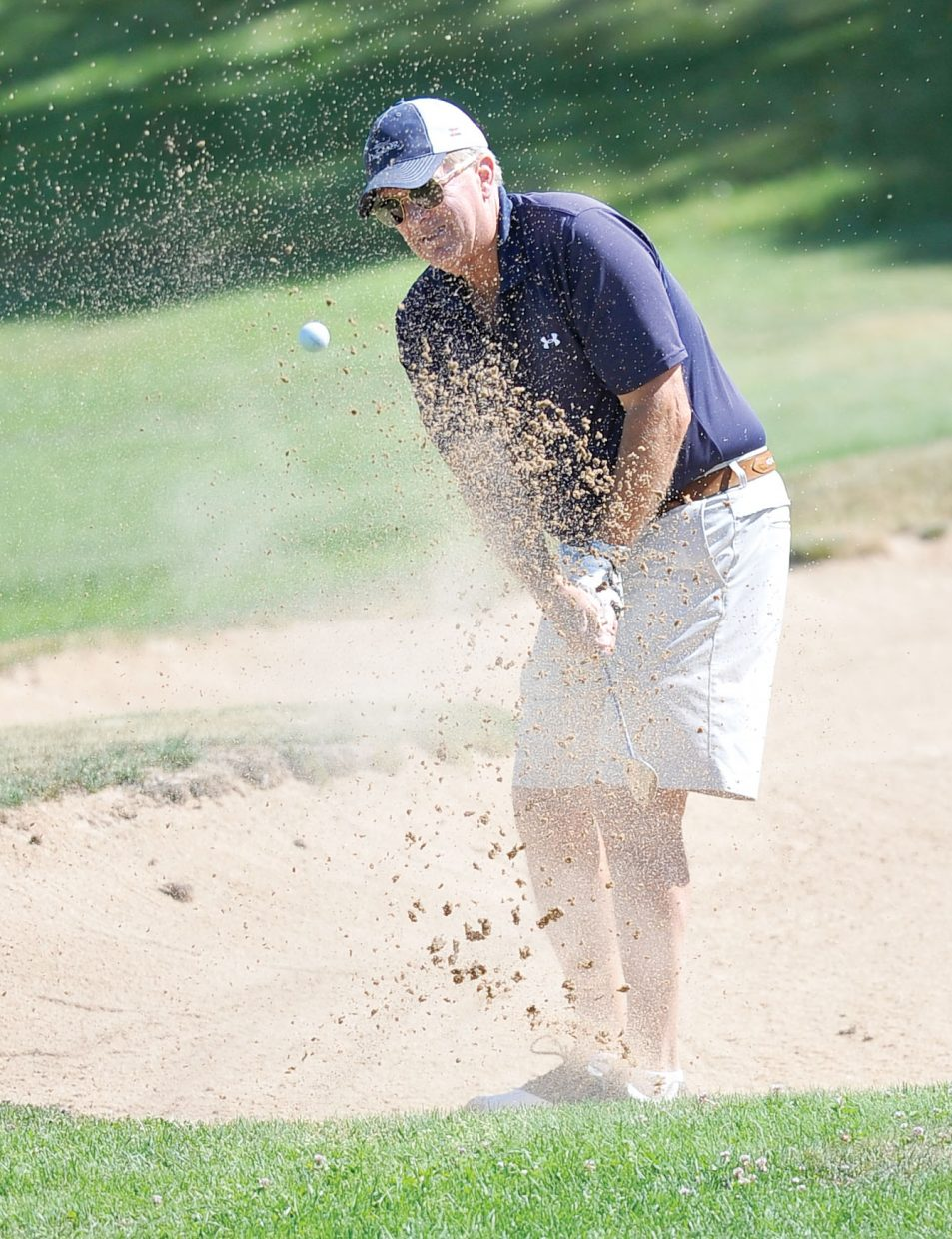 Bruce Hannon hits out of the sand at the 13th annual Rally for the Cure golf tournament at the Rollingstone Ranch Golf Club.