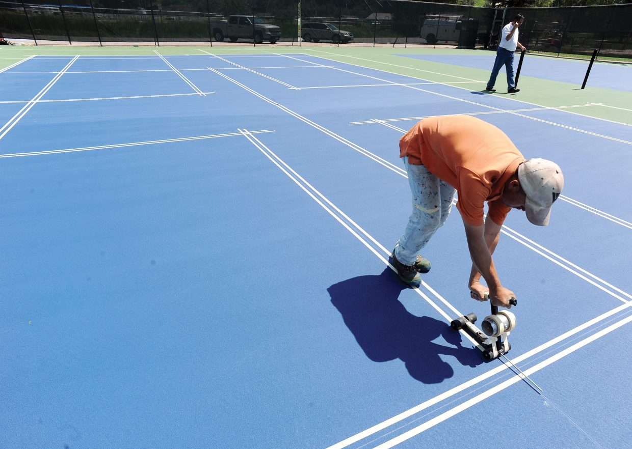 Epigmenio Barron tapes before painting lines for a new pickleball court on the recently resurfaced tennis courts at Howelsen Hill. Coatings resurfaced the public tennis courts and added four pickleball courts to the existing space. The lines for the pickleball courts were painted over the top of one of the tennis courts in a different color.