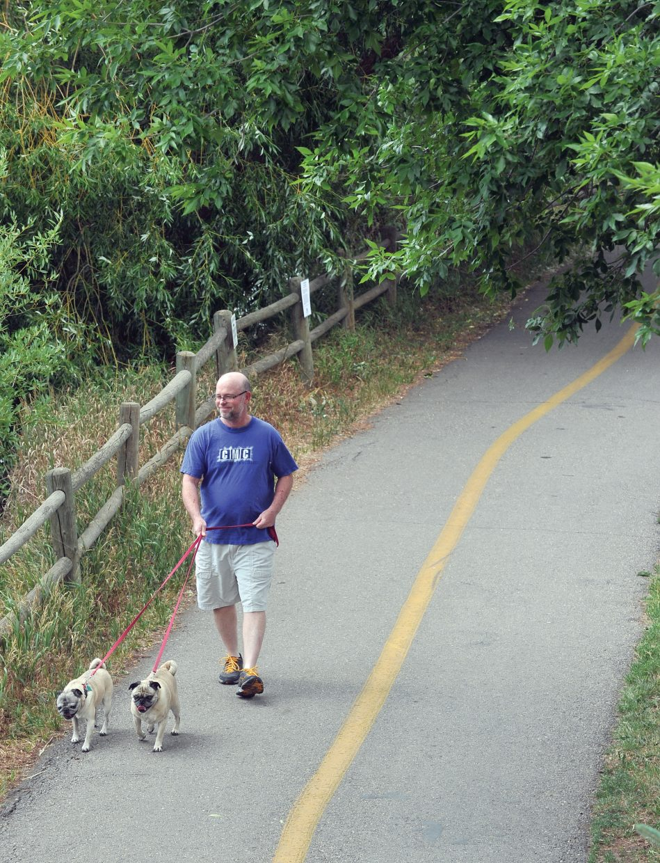 Bruce Beckum walks his dogs Daisy, left, and Max on Wednesday afternoon along the Yampa River Core Trail in Steamboat Springs.