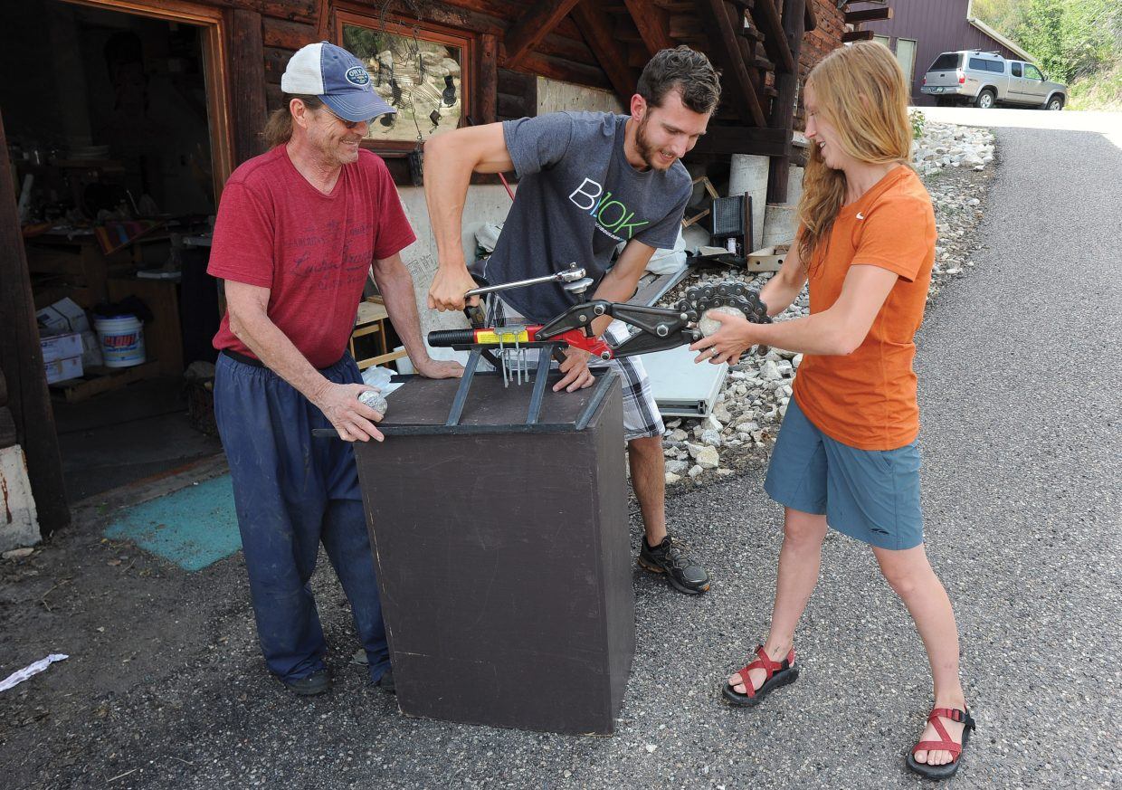 Leo Atkinson, far left, works with his son Dusty and daughter Siara to crack a geode at their Steamboat Springs shop. The family has been cracking geodes at Art in the Park for the past 10 years.