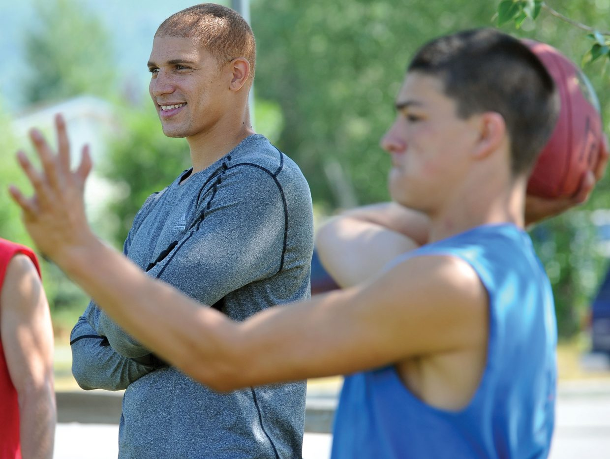 New Orleans Saints tight end Jimmy Graham visits with high school players Thursday morning during an informal workout on the field in front of Steamboat Springs High School.