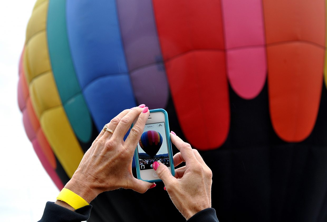 Lisa Jones snaps a photo of a hot air balloon on Saturday morning before it took off near Bald Eagle Lake. Steamboat's Hot Air Balloon Rodeo drew a large crowd that was eager to get snapshots.