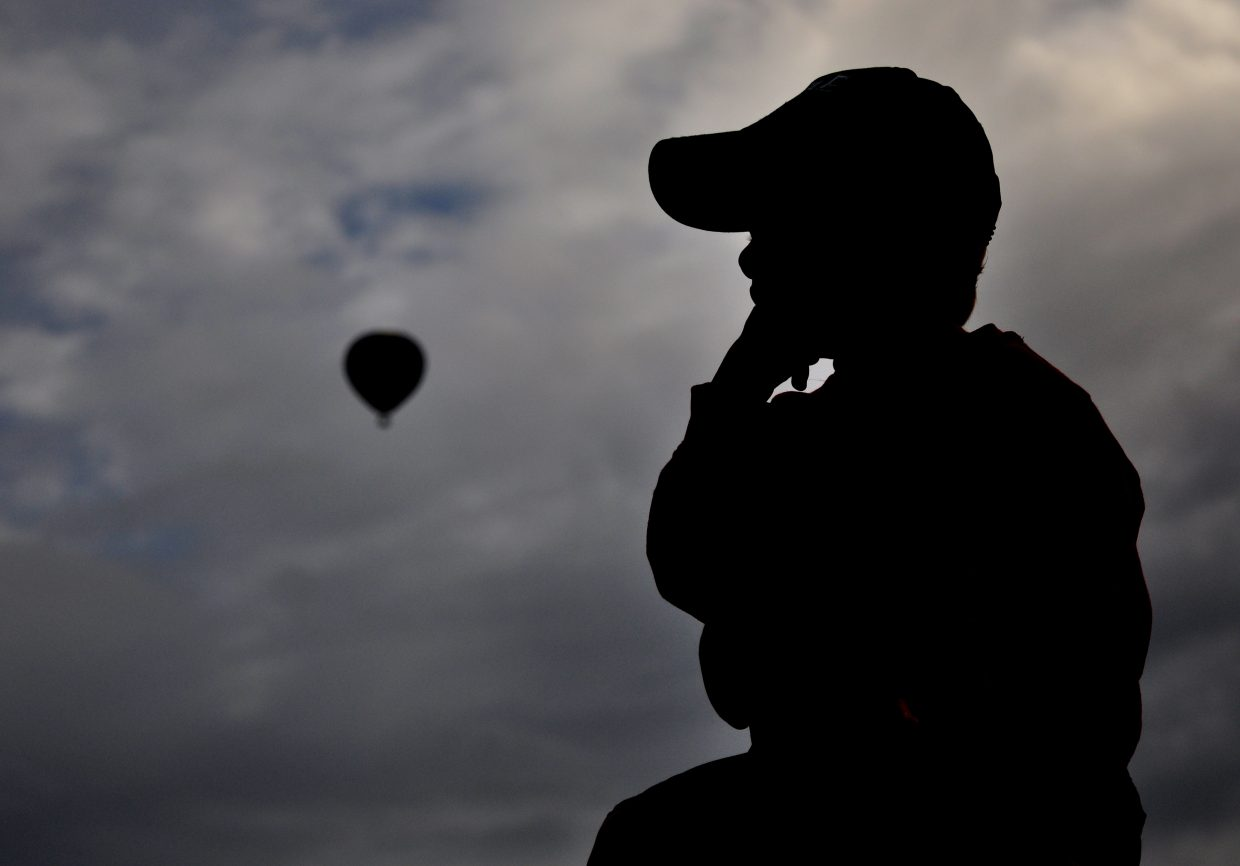 Trey Nelson, of Silverthorne, watches as hot air balloons take off Saturday at Bald Eagle Lake.