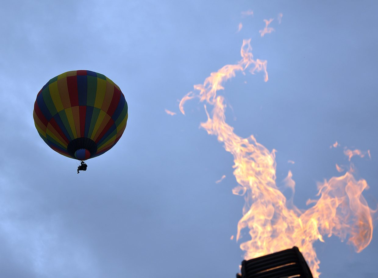 A balloon floats above Bald Eagle Lake on Saturday as a pilot tests the burners of another hot air balloon on the ground.
