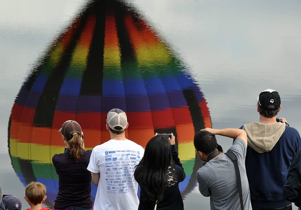 A crowd snaps photos of a balloon as it is reflected in the water of Bald Eagle Lake.