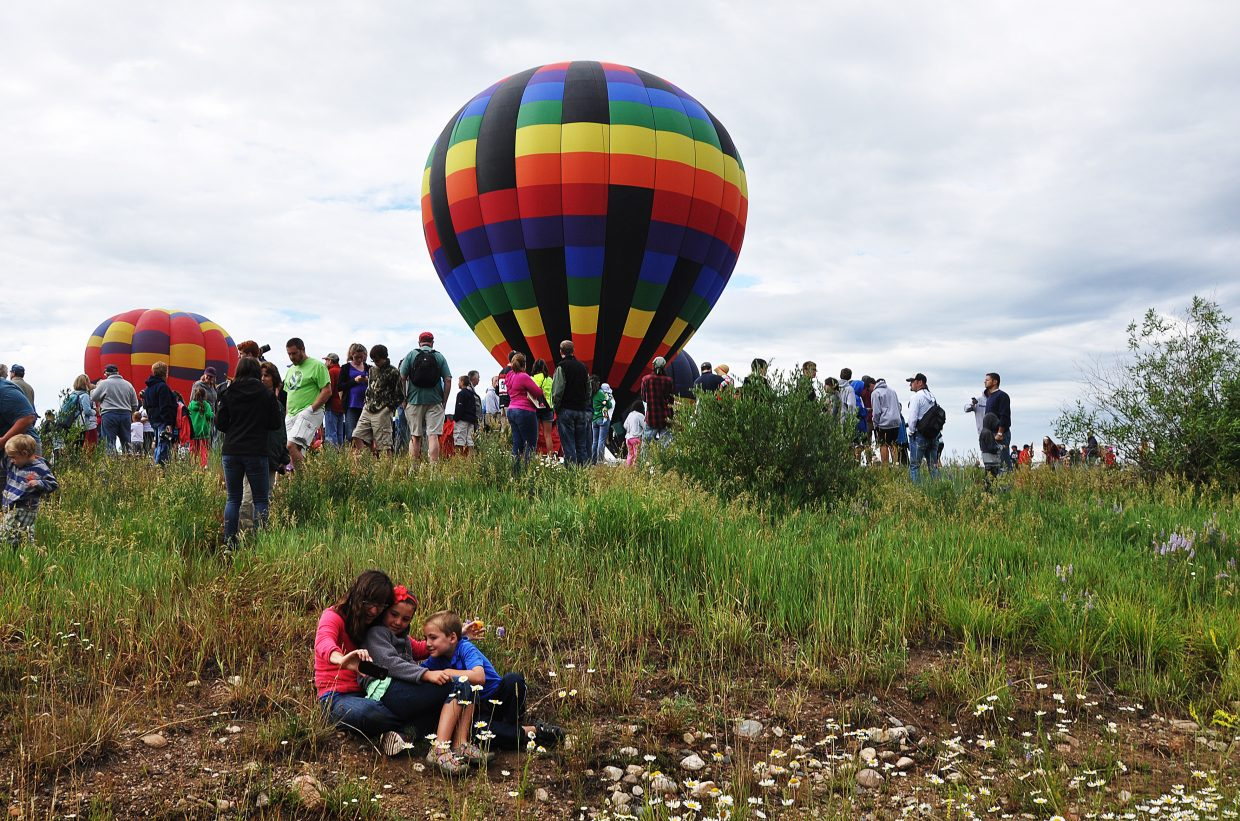 A family snaps a photo of themselves in front of a hot air balloon on Saturday at Bald Eagle Lake.