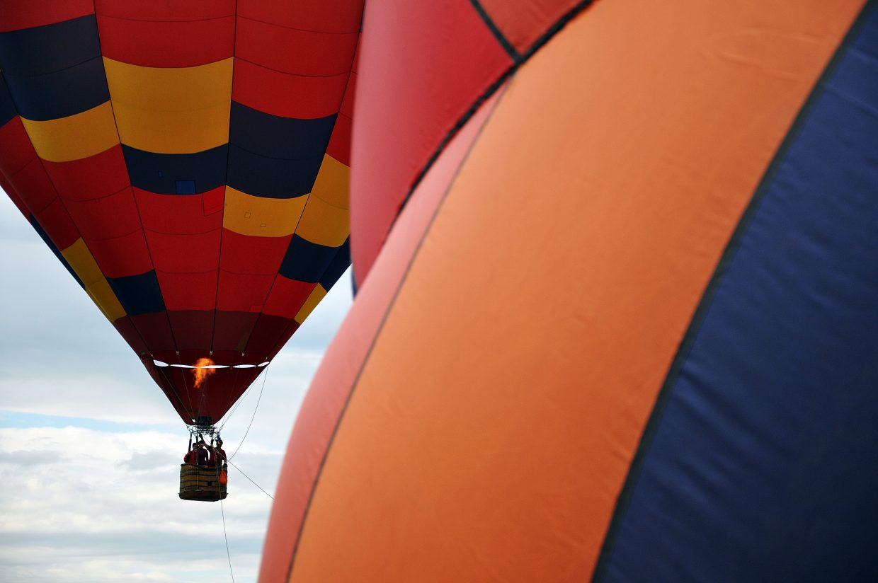 A hot air balloon takes off as another inflates Saturday at Bald Eagle Lake.