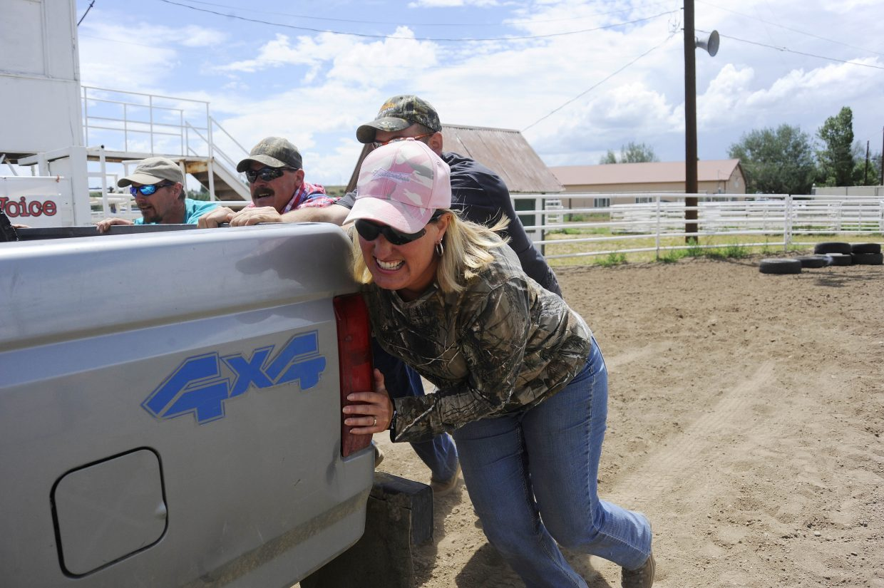 Kay Brooks struggles as she helps her team push a truck during the Routt County Redneck Olympics on Saturday at the Routt County Fairgrounds in Hayden.
