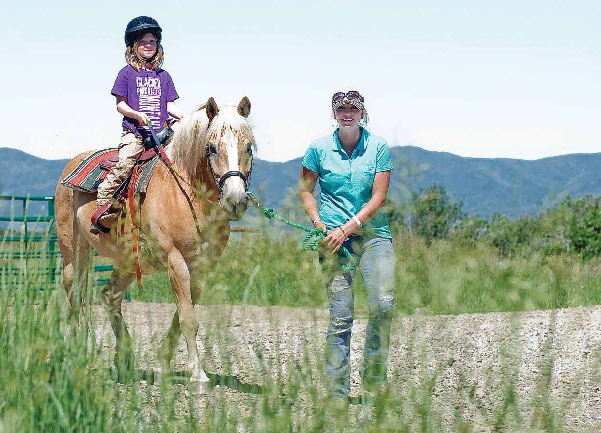 Zuzu Gibbs is lead by Danielle Haxton, youth activities instructor for the CR Summit Riding Camp, while riding Benny Buttons at a horseback riding camp for the Parks, Open Space and Recreational Services Department. Eight young riders took part in the four-day riding camp at the CR Summit Riding Camp just outside of Steamboat Springs where they learned how to take care of and ride horses.