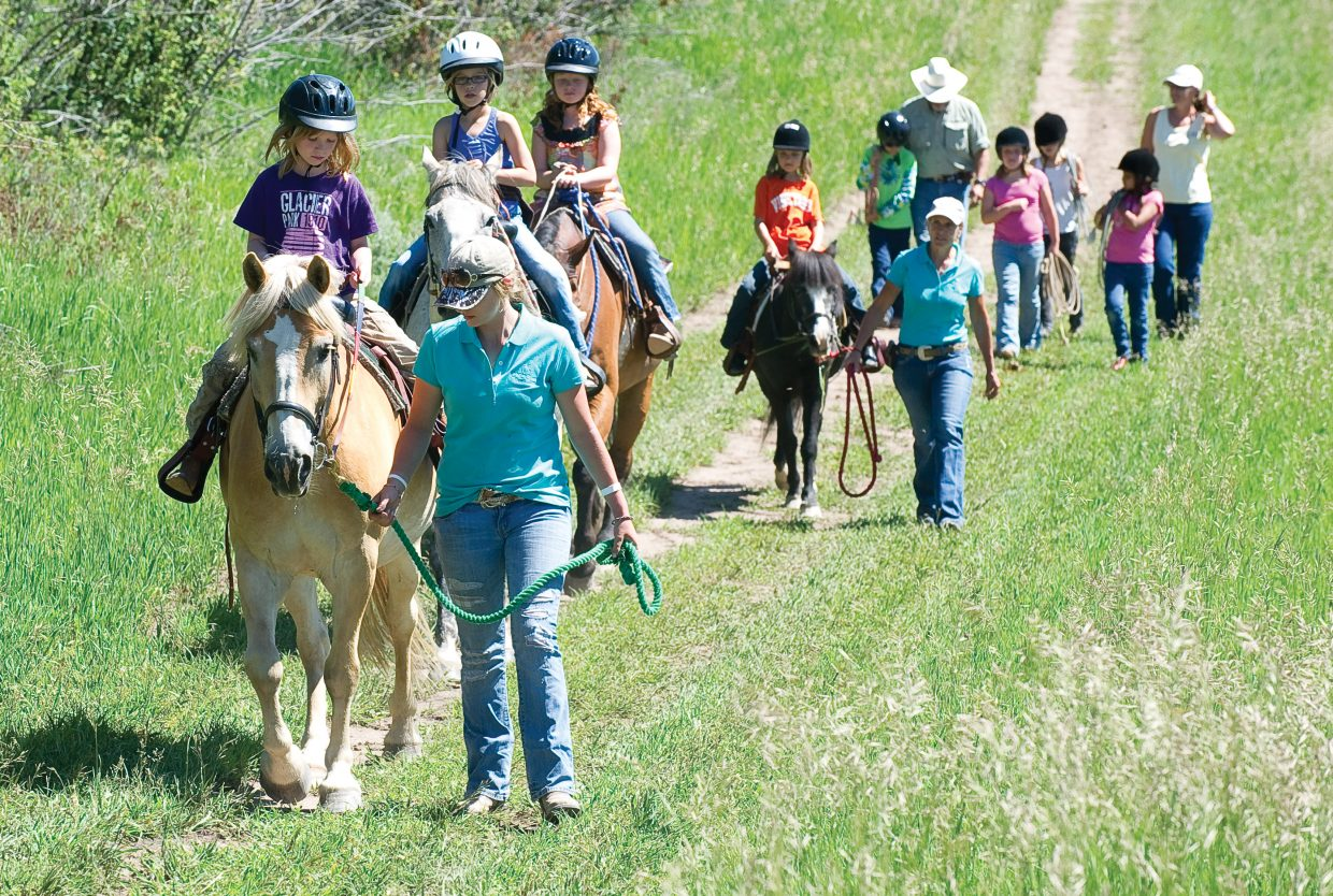 Danielle Haxton, youth activities instructor for the CR Summit Riding Club, leads a group of youngsters on a trail ride at the ranch just outside of Steamboat Springs.