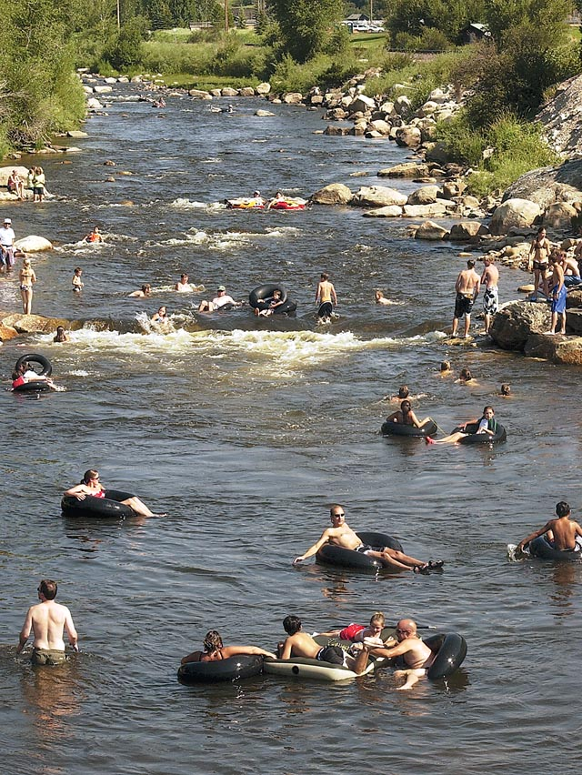 The Yampa River continues to attract those people filling the river to help with cool down, wading, tubing, sunning and just playing Monday near the 13th Street Bridge.