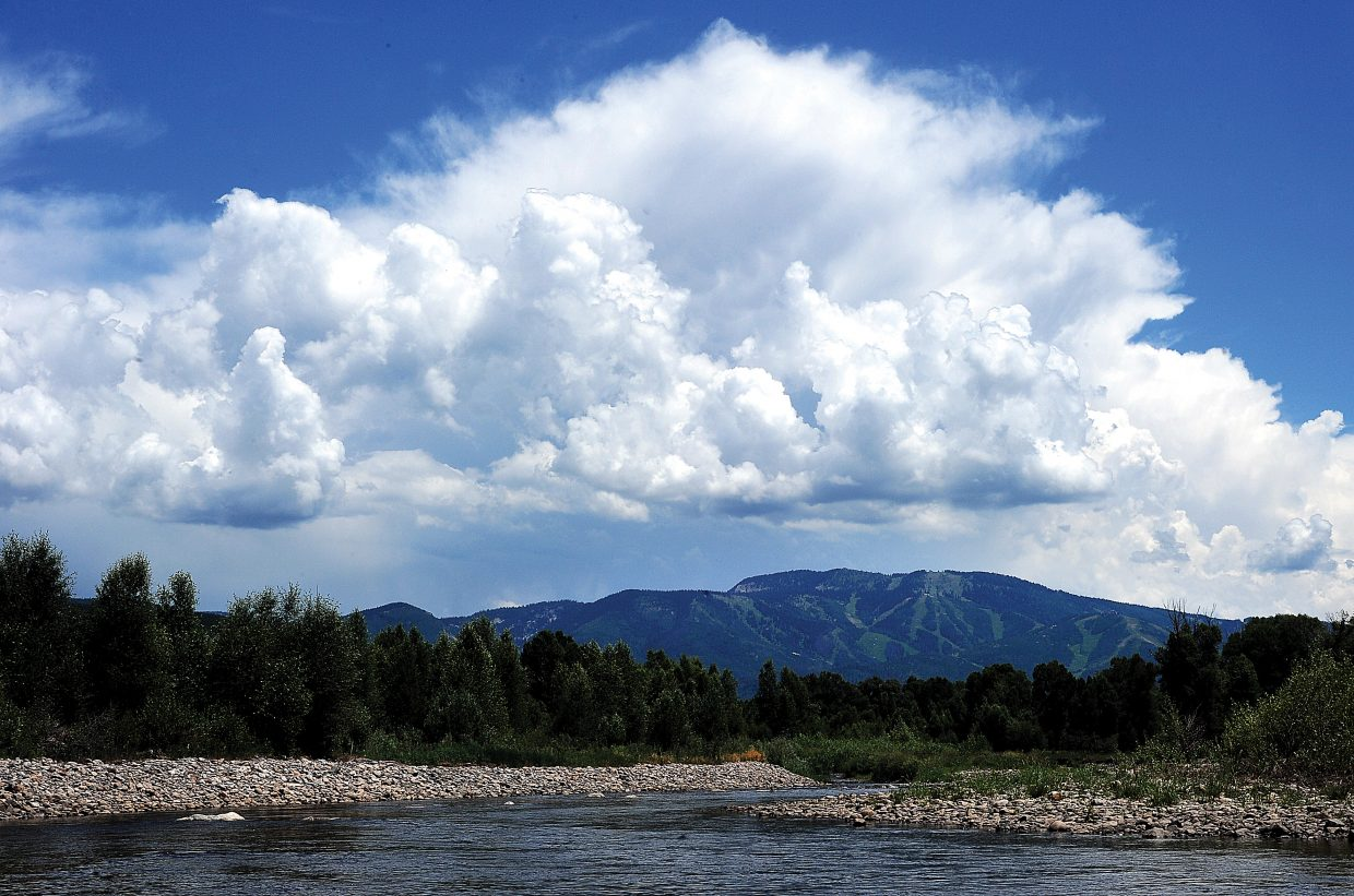Storm clouds build over Mount Werner on Thursday as the cool waters of the Yampa River continue to flow downstream.