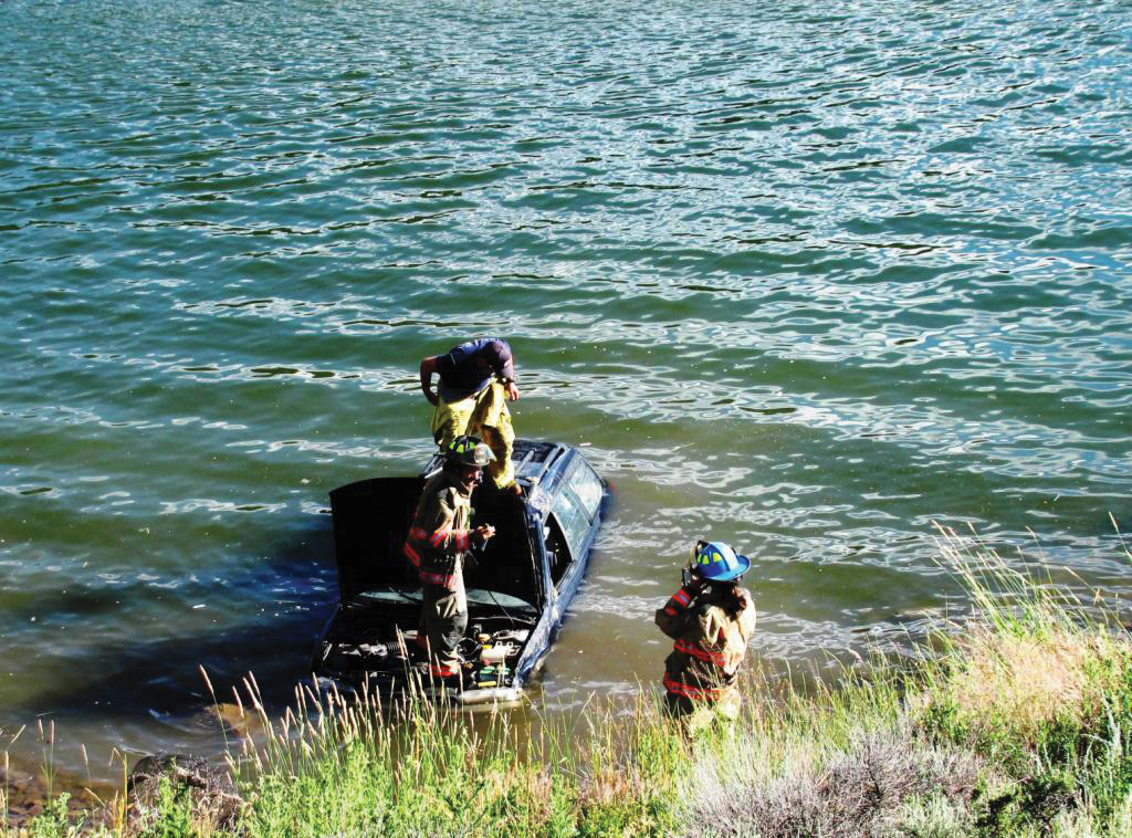 Firefighters disconnect a car's electrical supply while preparing to tow it out of Stagecoach Reservoir on Wednesday. The two occupants of the car were not seriously injured in the accident.