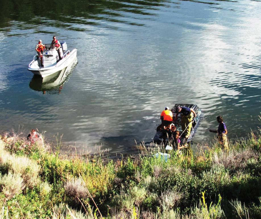 Oak Creek Fire Protection District firefighters and Stagecoach State Park personnel prepare to tow a car out of the reservoir Wednesday afternoon.