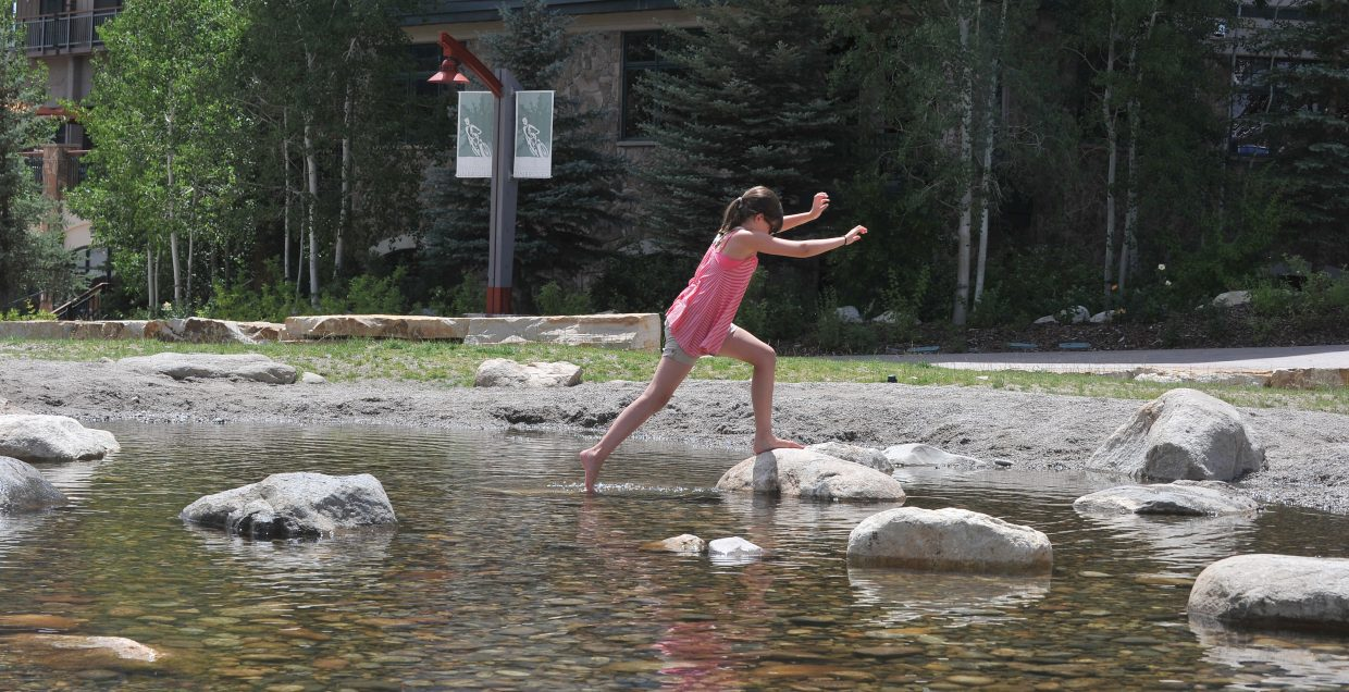 Maria Mohajir, of Lawrence, Kan., jumps across Burgess Creek on Thursday afternoon while visiting Steamboat Ski Area.