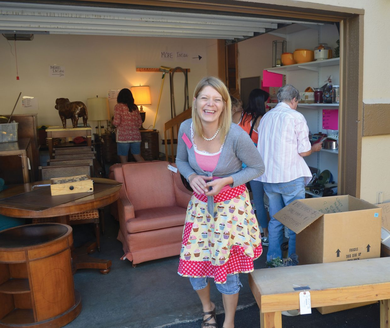Jackie Andrews, of Annie's Home Consignment, keeps it fun with a 1950s-style kitchen apron during an estate sale Friday in a townhome near the ski mountain in Steamboat Springs.