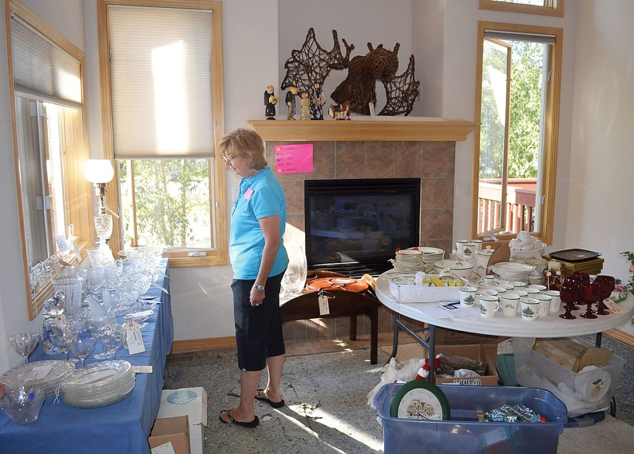 Missy Beirne admires a collection of cut glass and crystal during Friday's estate sale. The moose head made of twigs over the fireplace sold for $55.