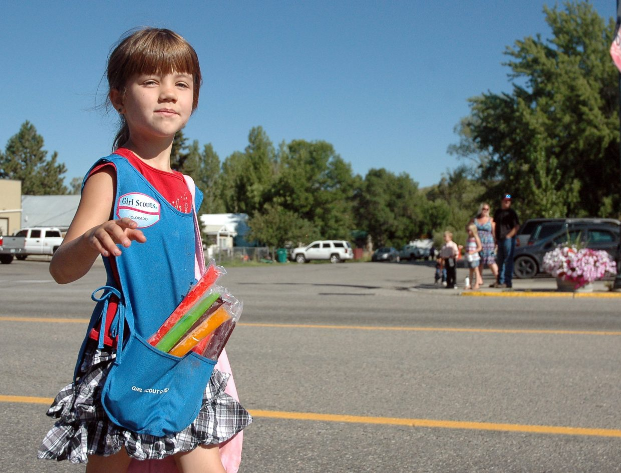 Isabelle Mathey, 7, waves as she hands out ice pops at the annual Hayden Daze parade Saturday morning. The event continued with activities, music and a barbecue at Dry Creek Park.