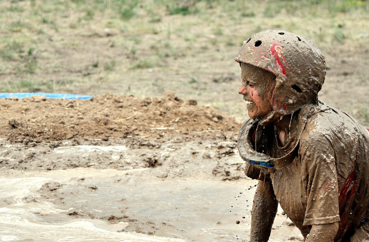 Anthony Mathey climbs out of a mud pit Saturday during the Mud Surfing competition at the Routt County Redneck Olympics in Hayden.