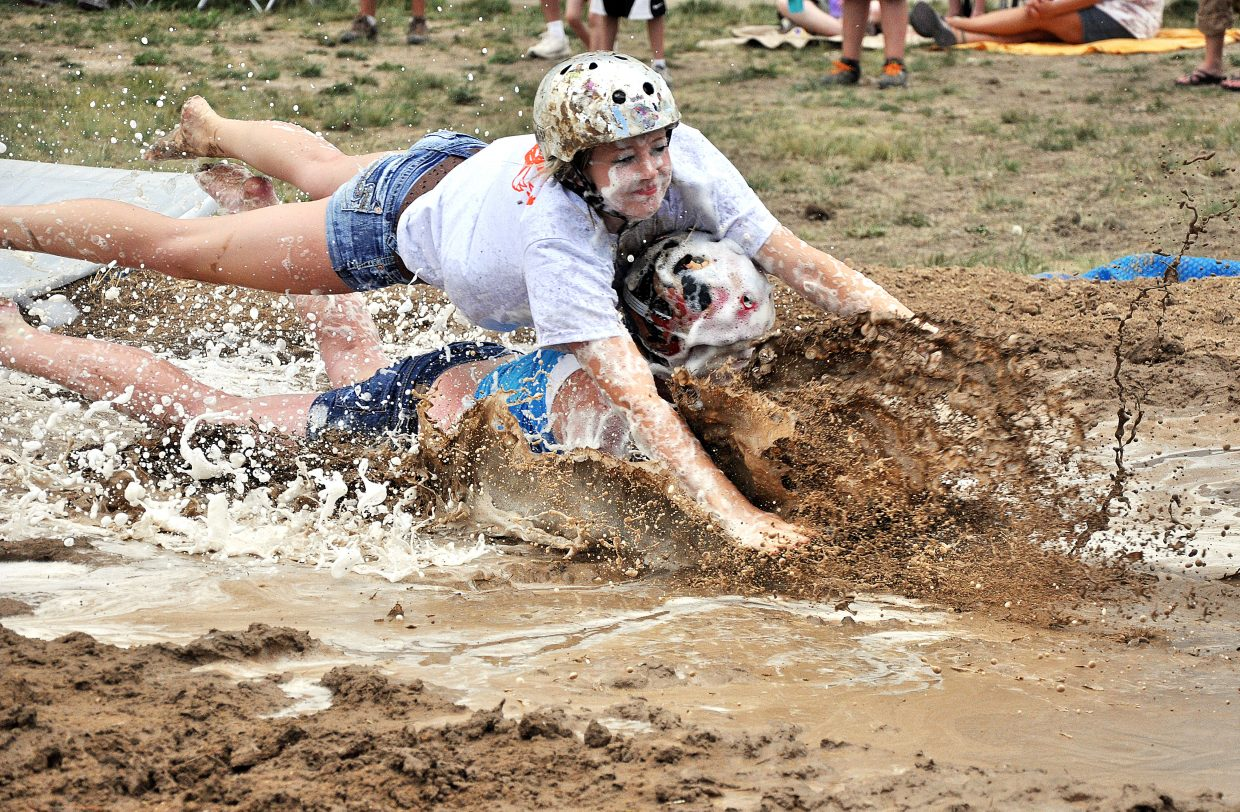 Miranda Watts, top, and Jori Cless fly into a mud pit Saturday during the Routt County Redneck Olympics in Hayden.