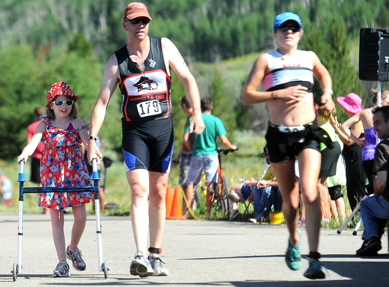 Jim Knapp helps his daughter, Katherine, 8, across the finish line of Sunday's Steamboat Lake Sprint Triathlon. Katherine underwent surgery two months ago and just got back on her feet a week before the race.