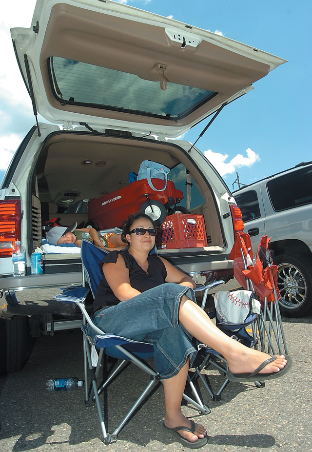 Cynthia Rocha escapes Friday's heat in the shade from the tailgate of her sports utility vehicle in the parking lot at Howelsen Hill. Rocha's 2-year-old son, Alex, was napping in the back between games at the Triple Crown Baseball World Series.