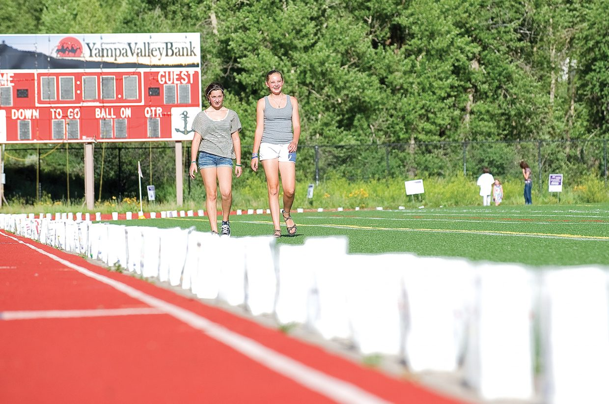 Jenna Skubic, left, and Anna Miller walk across Gardner Field after placing luminaries on the track as part of the 2011 Relay for Life in Steamboat Springs Friday night.