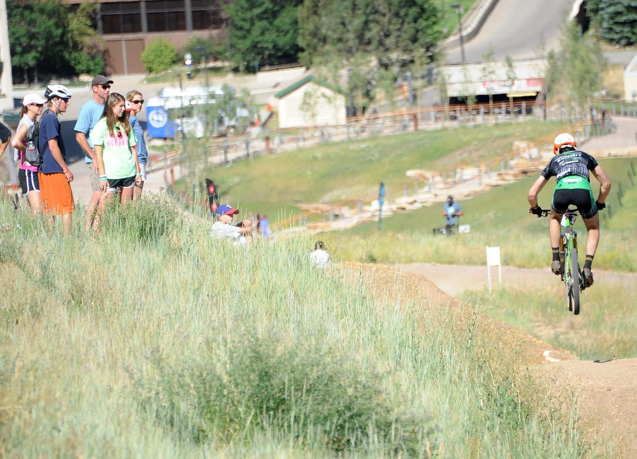 Onlookers watch riders in the Buff Pass Enduro hit a jumps trail on Sunday in Steamboat Springs.