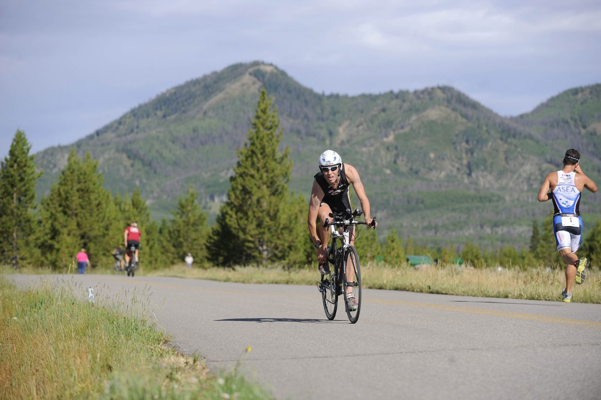 Andy Bartosch returns to the transition area, while eventual winner Cody Waite starts his run Sunday at the Steamboat Sprint Triathlon.