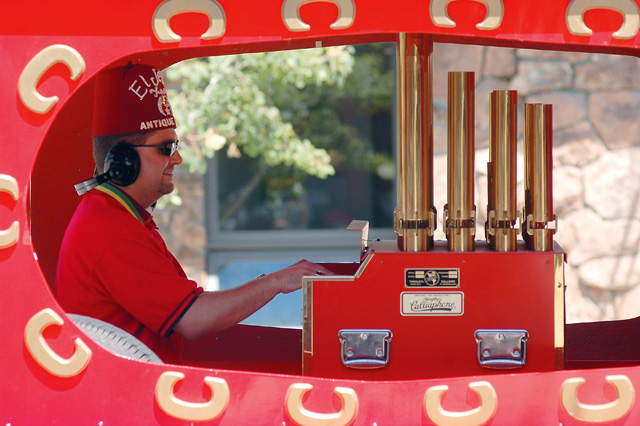 A Shriner plays an organ in the back of a van during the parade.