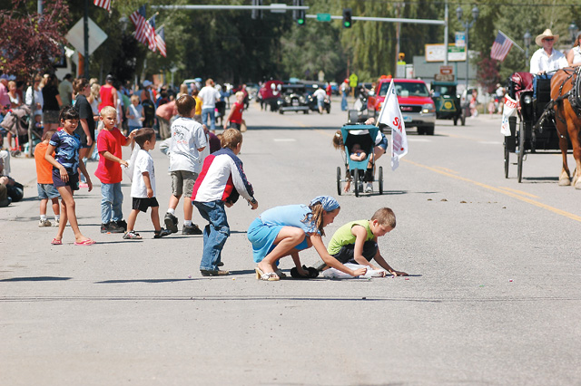 Children rush onto Jefferson Avenue to gather candy during the Colorado Days parade.