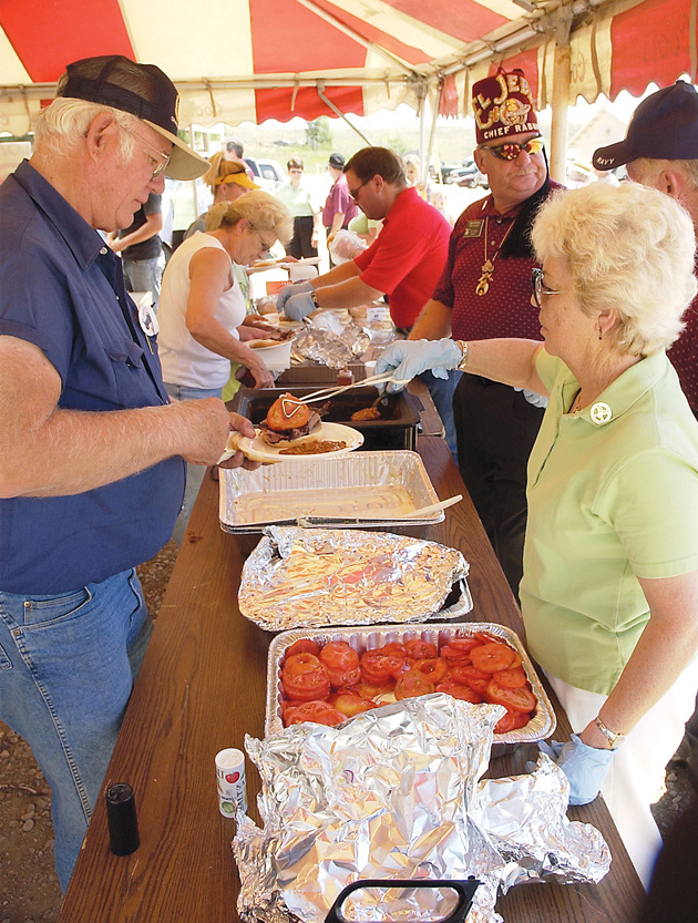 Ellen Dattilo serves Craig resident Fred Shaffer tomatoes to go with his sandwich at the Shriner's barbeque Saturday during Colorado Days.
