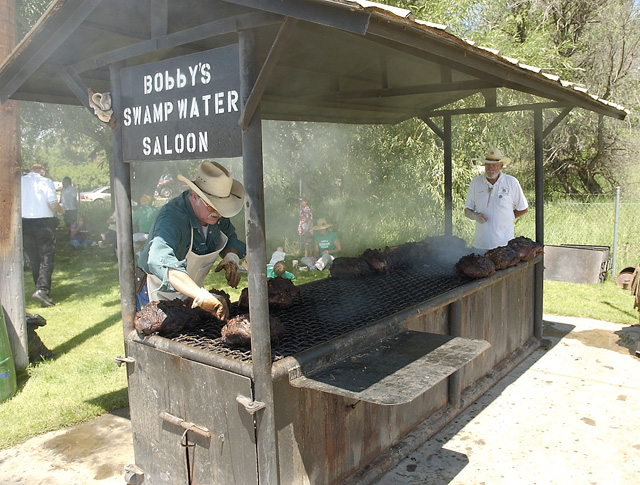 """Craig Resident Alan Bennett mans the grill at the Shriner's barbeque Saturday during Colorado Days. The top round beef was marinated with """"Bobby's Swamp Water"""" and cooked overnight."""