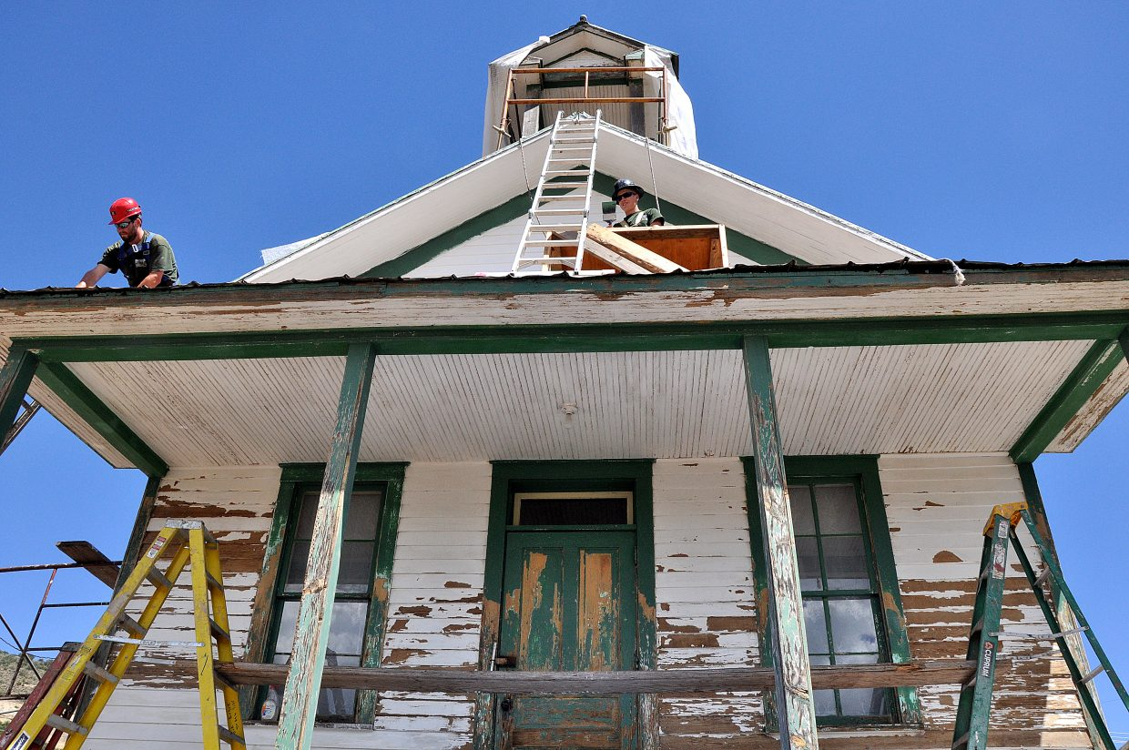 Rocky Mountain Youth Corps volunteers Kris Gayer, left, and Austin Bail work on the roof of the Foidel Canyon Schoolhouse on Monday afternoon. Historic Routt County is leading the effort to restore the structure that sits near Twentymile Coal Mine.