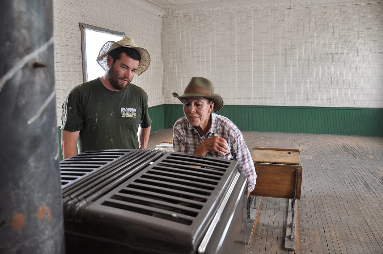 Harieta Nelson, right, and Rocky Mountain Youth Corps volunteer Kris Gayer examine the stove inside the Foidel Canyon Schoolhouse on Monday.