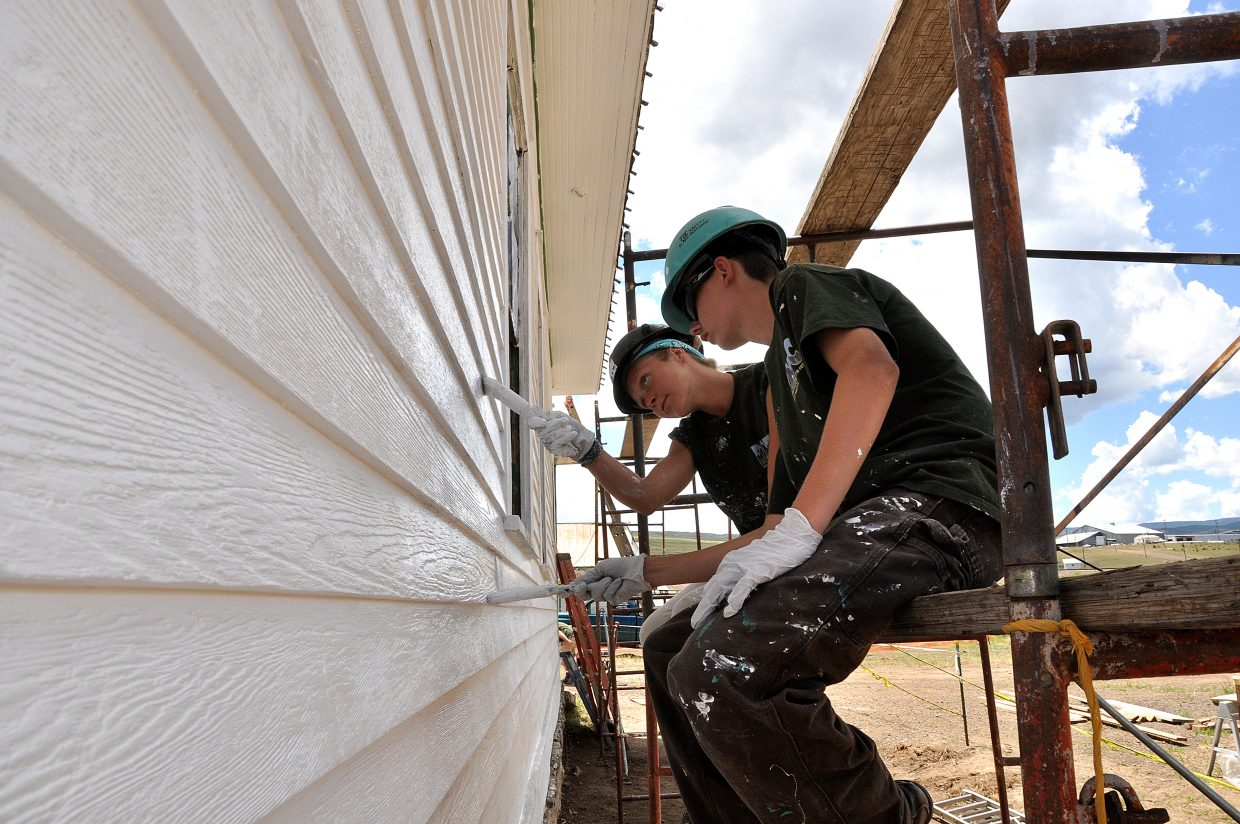 Rocky Mountain Youth Corps volunteers Taylor Zabel, front, and Allie Andrews paint the Foidel Canyon Schoolhouse on Monday afternoon.