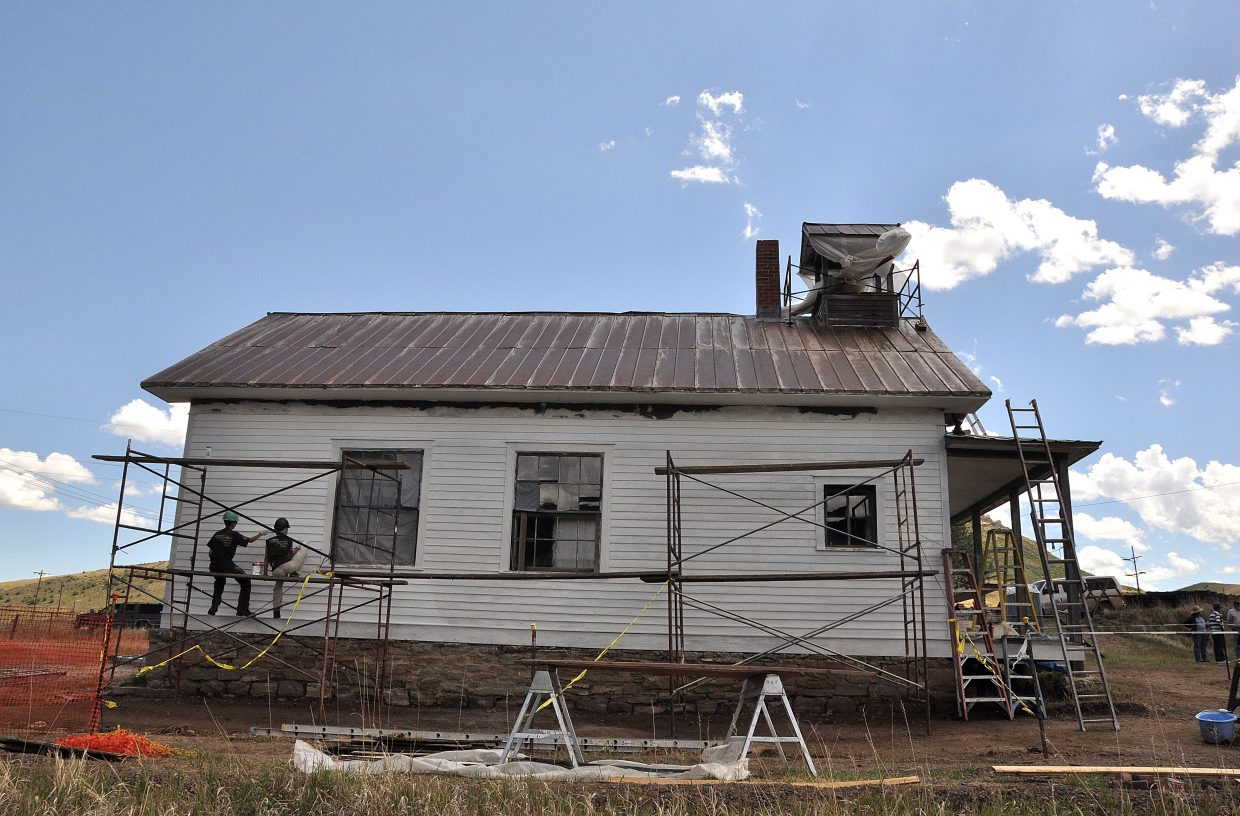 Rocky Mountain Youth Corps volunteers Taylor Zabel, left, and Allie Andrews paint the Foidel Canyon Schoolhouse on Monday afternoon.