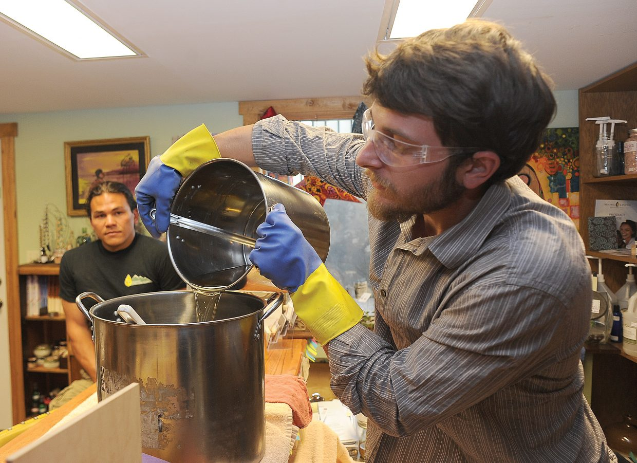 Dan Fernandez pours ingredients for Summit Soap into a metal pot Tuesday during a demonstration at Kneading Hands on Oak Street in Steamboat Springs. Fernandez and Dara Lor, background, own Summit Greasecycling, which collects and purifies the cooking oil that is used in Summit Soap.
