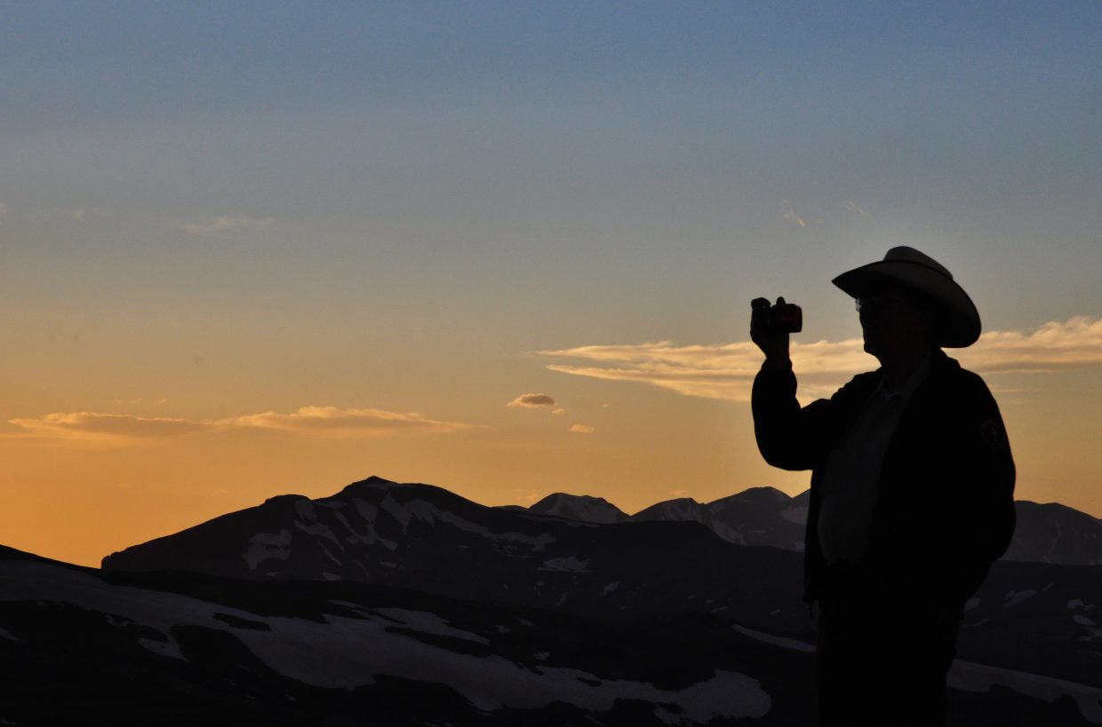 A man photographs the sunset from the Gore Range overlook in Rocky Mountain National Park.