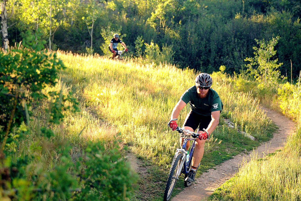 Matthew Doro rides through a sunlit meadow on Emerald Mountain during a Quarry Mountain Town Challenge race in Steamboat Springs.