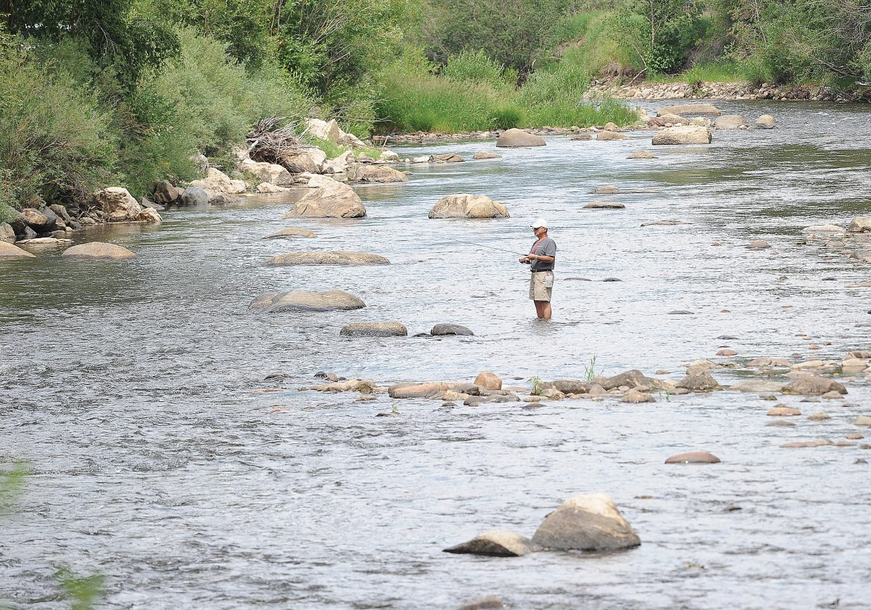 Dick Cassella fishes along the Yampa River on Thursday. Colorado Parks and Wildlife aquatic biologist Billy Atkinson is asking anglers to get their fishing in early each day because of high water temperatures after noon.
