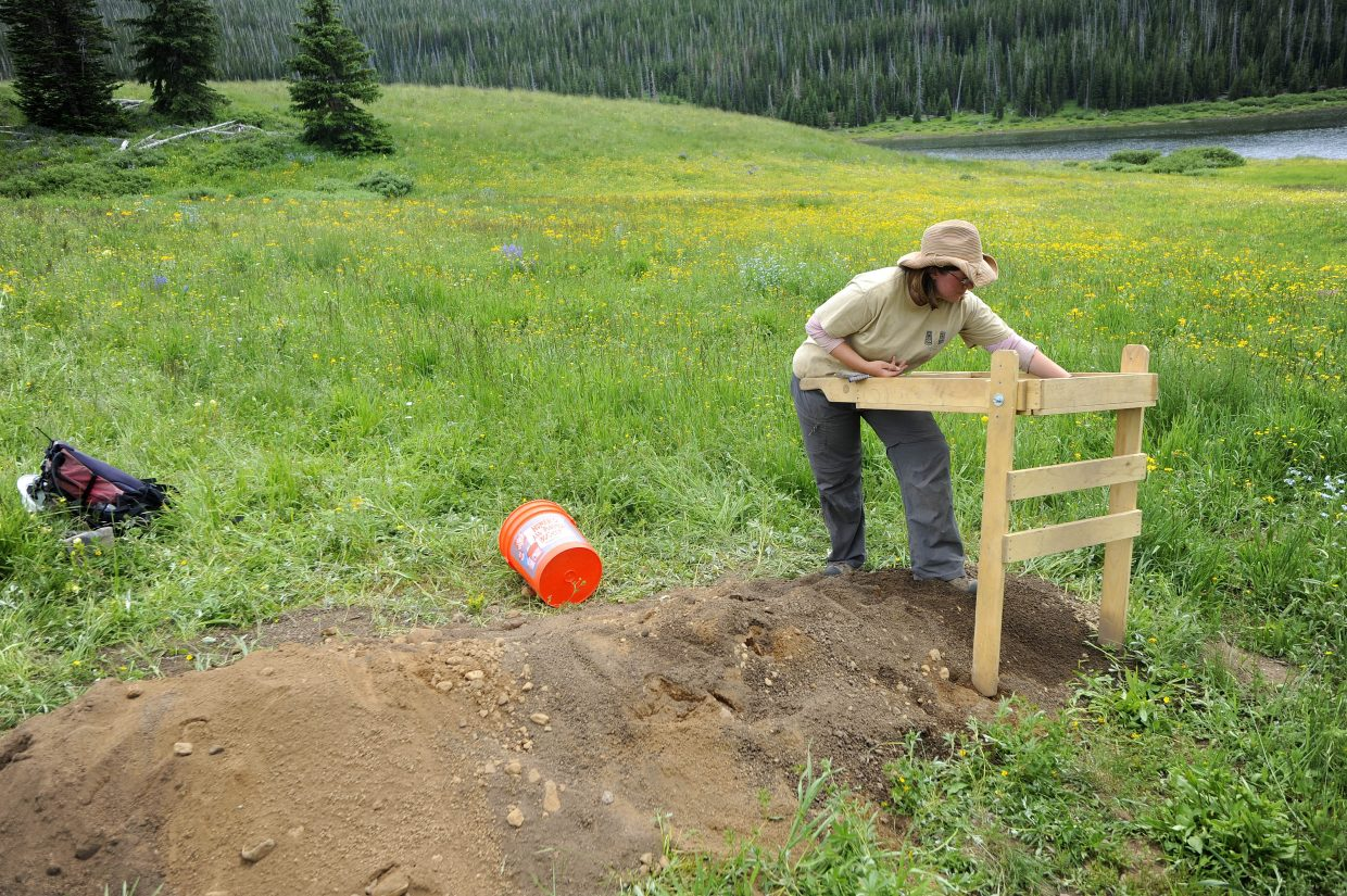 Steamboat Springs U.S. Forest Service archaeologist Bridget Roth runs dirt through a screen to look for artifacts.