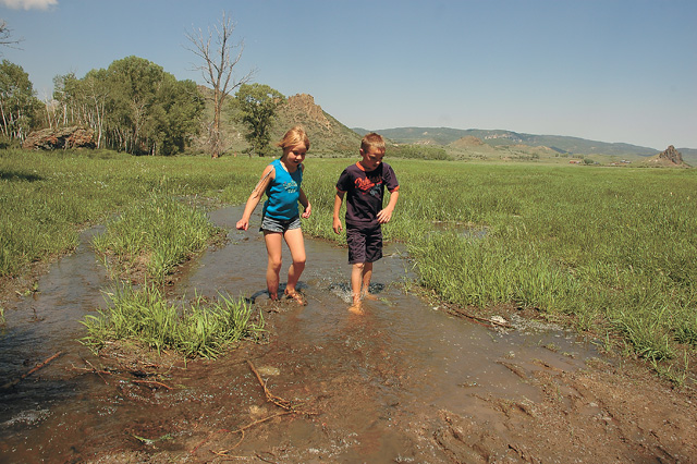 Nicole Derwent, 7, and Colten Zippay, 10, play in muddy water that overflows from the Stafford Ditch just north of Yampa on land owned by rancher Dean Rossi.
