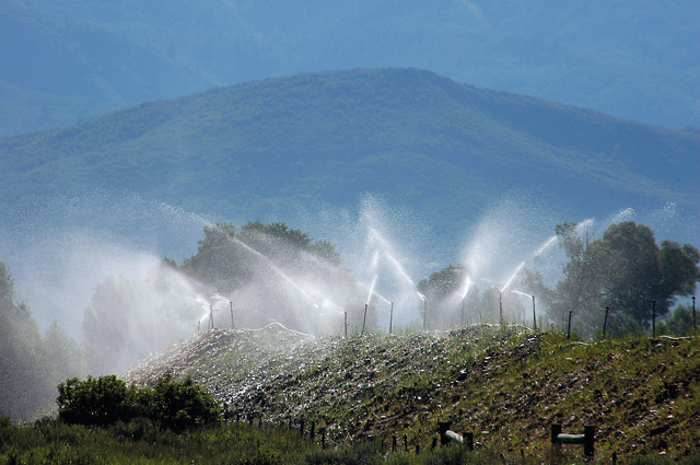 Large sprinklers water a seeded berm at the Duckles Gravel Pit west of Steamboat Springs.