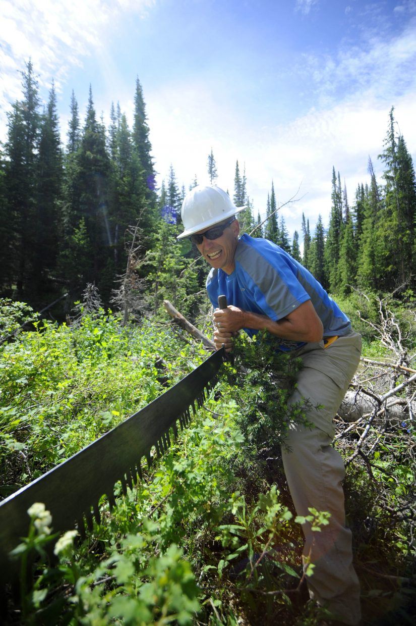 Crew member Neal Obray uses the vintage saw in Flat Tops Wilderness Area.