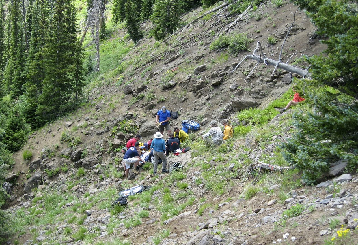Emergency responders help a man who fell down an embankment Tuesday while hiking toward the Devil's Causeway.