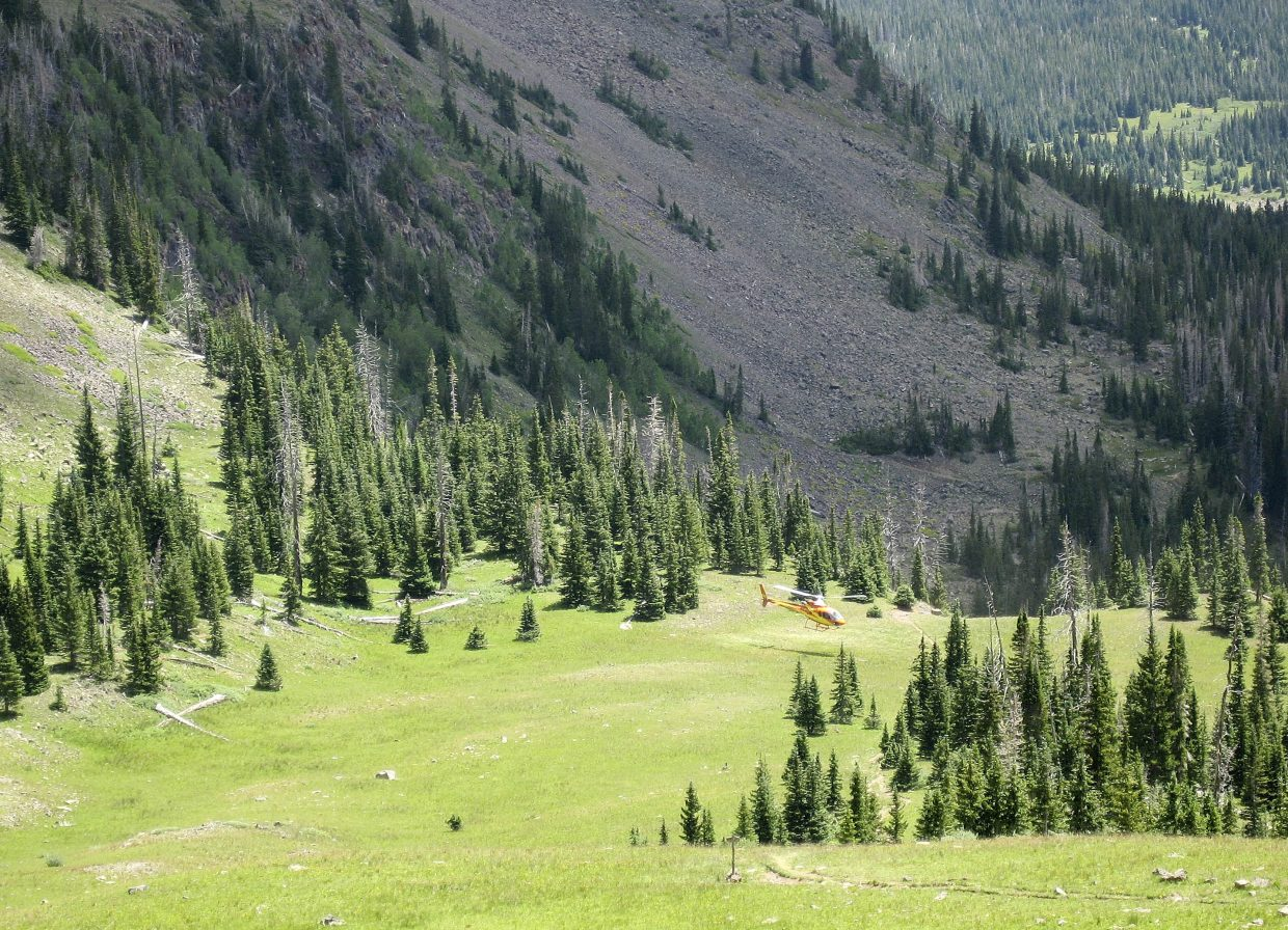 A helicopter lands to evacuate a man Tuesday from the Flat Tops Wilderness Area.
